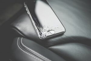 Smartphone mit gesplitterten Display liegt auf einem Leder Sessel