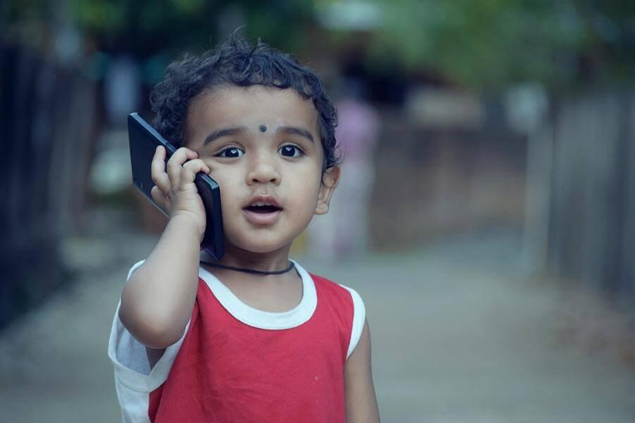 Kleiner Junge telefoniert mit einem Handy am Ohr